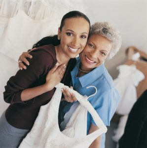 Portrait of a Smiling Bride Holding a Wedding Dress in a Clothes Shop Standing by Her Mother